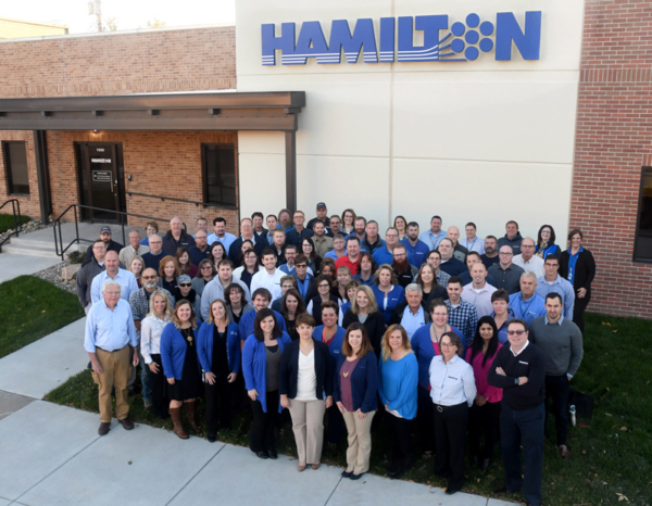 Hamilton team standing in front of the Aurora corporate office.