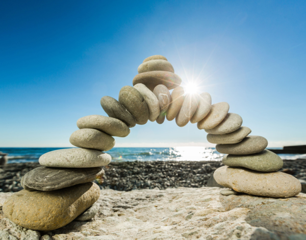 Arch of rocks stacked on a beach.